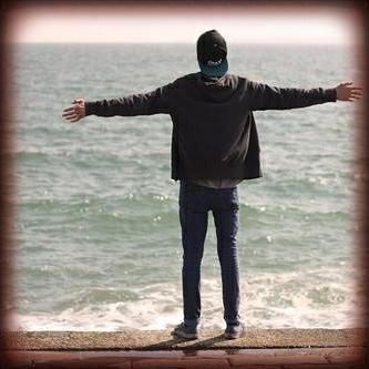 对着海边张开双手的男生背影头像图片
